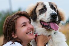 Ung lycklig flicka som kramar henne hund arkivbild
