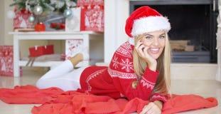 Ung lycklig flicka som ligger på den röda filten bredvid spisen Royaltyfria Foton