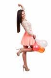 Ung lycklig flicka som rymmer en grupp av kulöra ballonger på vita lodisar Royaltyfri Foto
