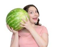Ung lycklig flicka som rymmer en vattenmelon som isoleras på vit bakgrund Arkivbild