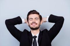 Ung lycklig gladlynt le man i den svarta dräkten som har en vila aft arkivfoto
