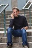 Ung lycklig grabb som talar på mobil, medan sitta på utomhus- trappa Royaltyfria Bilder