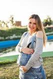 Ung lycklig gravid kvinna som kopplar av och tycker om liv i höstnatur fotografering för bildbyråer