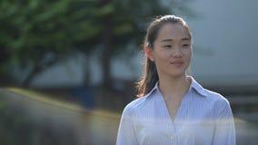 Ung lycklig härlig asiatisk affärskvinna som utomhus tänker lager videofilmer