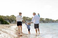 Ung lycklig härlig familj som tillsammans går på stranden som tycker om sommarferier Arkivbild