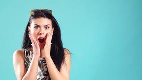 Ung lycklig härlig flicka som ler förvånansvärt på turkosbakgrund stock video