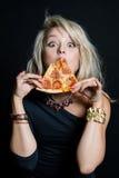Ung lycklig härlig kvinna som äter pizza royaltyfria bilder