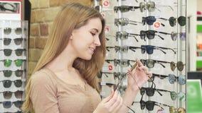 Ung lycklig härlig kvinna som väljer mellan två par av solglasögon arkivfilmer