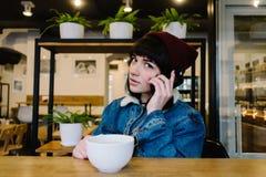 Ung lycklig hipsterflicka som talar på telefonen och dricker kaffe i ett trevligt kafé royaltyfria foton