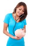 Ung lycklig härlig asiatisk kvinna som använder stetoskopet på henne som är piggy Arkivfoto