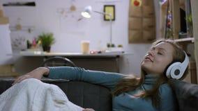 Ung lycklig kvinna att lyssna till musik på en soffa arkivfilmer