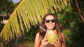 Ung lycklig kvinna för blandat lopp som dricker den nya thailändska kokosnötvattencoctailen på den tropiska stranden 4K phuket th arkivfilmer