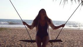Ung lycklig kvinna i baddräkt och skjorta som kopplar av på gunga på den tropiska havstranden Härligt flickasammanträde på gunga  stock video