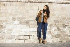 Ung lycklig kvinna i brunt läderomslag royaltyfri bild