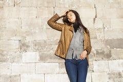 Ung lycklig kvinna i brunt läderomslag arkivbild