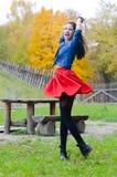Ung lycklig kvinna i den korta röda kjolen som omkring rotera Arkivfoton