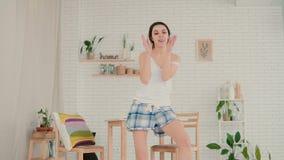Ung lycklig kvinna i pyjamas som hemma dansar Attraktiv flickade rika som är rolig i köket långsam rörelse stock video