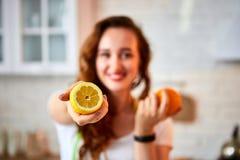 Ung lycklig kvinna med apelsin- och citroncitruns i modernt kök Sunt mat- och bantabegrepp lossa vikt arkivbilder