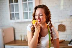Ung lycklig kvinna med apelsin- och citroncitruns i modernt kök Sunt mat- och bantabegrepp lossa vikt royaltyfri fotografi