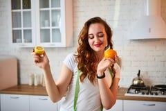 Ung lycklig kvinna med apelsin- och citroncitruns i modernt kök Sunt mat- och bantabegrepp lossa vikt royaltyfri bild