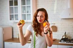Ung lycklig kvinna med apelsin- och citroncitruns i modernt kök Sunt mat- och bantabegrepp lossa vikt arkivbild