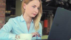 Ung lycklig kvinna med bärbara datorn i kafét stock video