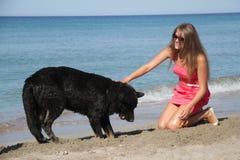 Ung lycklig kvinna med den svarta hunden Royaltyfria Bilder