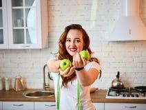 Ung lycklig kvinna med det gröna äpplet i modernt kök Sunt mat- och bantabegrepp lossa vikt royaltyfria bilder