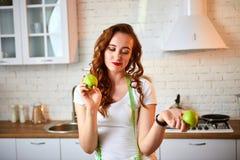 Ung lycklig kvinna med det gröna äpplet i modernt kök Sunt mat- och bantabegrepp lossa vikt arkivfoto