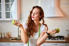 Ung lycklig kvinna med det gröna äpplet i modernt kök Sunt mat- och bantabegrepp lossa vikt arkivfoton