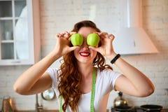 Ung lycklig kvinna med det gröna äpplet i modernt kök Sunt mat- och bantabegrepp lossa vikt arkivbilder