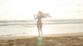 Ung lycklig kvinna med halsdukspring på havstranden på solnedgången tycka om flickasommar Kvinnlig i bikini med flyg Royaltyfri Fotografi