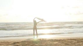 Ung lycklig kvinna med halsdukspring på havstranden på solnedgången tycka om flickasommar Kvinnlig i bikini med flyg Arkivfoto