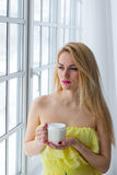 Ung lycklig kvinna med koppkaffe 8 mars Arkivbild