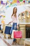 Ung lycklig kvinna med några shoppingpåsar i gallerian royaltyfri fotografi