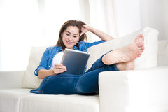 Ung lycklig kvinna på den hemmastadda tyckande om användande digitala minnestavladatoren för soffa Royaltyfri Fotografi