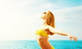 Ung lycklig kvinna på stranden i en bikini Royaltyfri Bild