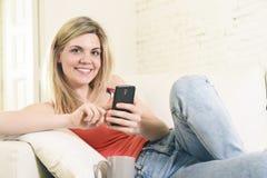 Ung lycklig kvinna som är bekväm på den hem- soffan genom att använda internet app på mobiltelefonen royaltyfri foto