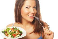 Ung lycklig kvinna som äter sallad. royaltyfri bild