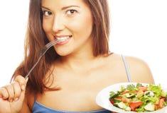 Ung lycklig kvinna som äter sallad. fotografering för bildbyråer