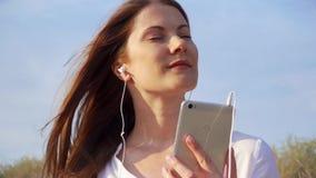 Ung lycklig kvinna som använder mobilen mot blå himmel Lyssnande musik för kvinnlig via mobiltelefonen i ultrarapid stock video
