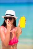 Ung lycklig kvinna som applicerar solkräm på henne Fotografering för Bildbyråer