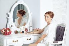 Ung lycklig kvinna som framme sitter av spegeln och förbereder sig oss royaltyfri foto
