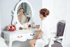 Ung lycklig kvinna som framme sitter av spegeln och förbereder sig oss arkivbild
