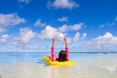 Ung lycklig kvinna som kopplar av på luftmadrassen under fotografering för bildbyråer