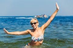 Ung lycklig kvinna som poserar i havsvatten royaltyfria bilder