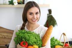 Ung lycklig kvinna som rymmer den pappers- påsen full av grönsaker och frukter, medan le Flickan har gjort shopping och ordnar ti royaltyfri bild