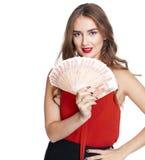 Ung lycklig kvinna som rymmer en fan av pengar som isoleras över vita lodisar royaltyfria bilder