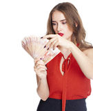 Ung lycklig kvinna som rymmer en fan av pengar som isoleras över vita lodisar arkivbilder