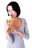 Ung lycklig kvinna som rymmer ett exponeringsglas av öl Royaltyfri Fotografi
